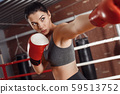 Boxing. Woman boxer in gloves practising hit on ring concerned 59513752