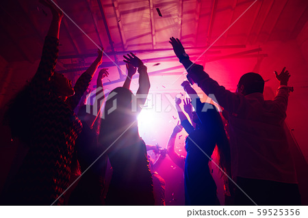 A crowd of people in silhouette raises their hands against colorful neon light on party background 59525356