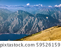 View on Alps and a paraglider over Garda lake from the mountain Monte Baldo, Lombardy, Italy. 59526159