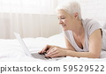 Senior lady browsing on laptop, resting on bed 59529522