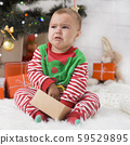 Little baby elf with present box crying near Xmas tree 59529895