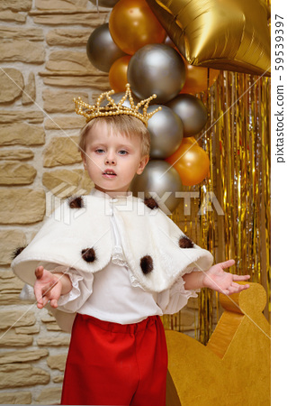 Little boy dressed as king with crown 59539397