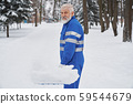 Portrait of cleaner in overalls with snow shover. 59544679