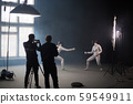 A fencing training in the studio - two women in protective costumes having a duel - two cameramans 59549911