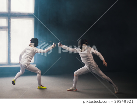 A fencing training in the studio - two women in protective costumes having a duel - poking with a 59549921