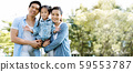 Asian family has a father, mother, and daughter smiling happy in the park dur 59553787
