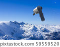 Skier Snowboarder jumping through air with sky in 59559520