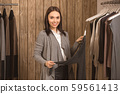 Young adult girl choosing wear in shopping mall 59561413