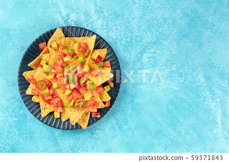 Mexican nachos, tortilla chips with tomato, avocado, and cilantro leaves, top-down shot on a blue 59571843