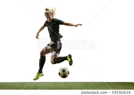 Female soccer player kicking ball at the stadium 59580839
