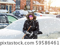 Woman wiping snow car using brush a winter morning 59586461