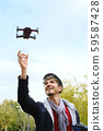 Young Man With Remote Control Landing Drone In His Hands 59587428