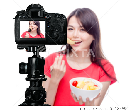 Asian food vlogger with fruit salad behind camera 59588996