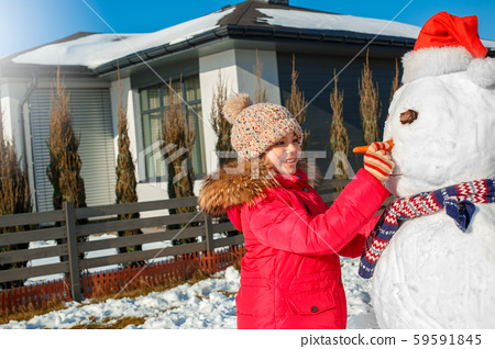 Winter vacation. Girl standing outdoors near house making snowman nose with carrot smiling happy 59591845