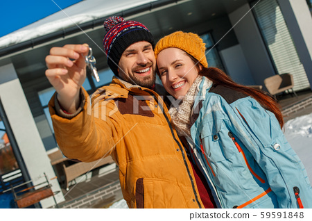 Winter vacation. Young couple standing together outdoors with keys from new apartment smiling happy 59591848