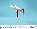 Girl in kimono practicing kick foot forward. 59593629