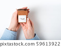 Open brown jewelry box with ring in female hand. 59613922