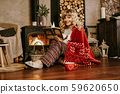 Happy young woman reading book in front of christmas interior with fireplace 59620650