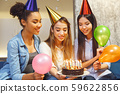 Group of friends having party indoors fun together ready to make a wish 59622856