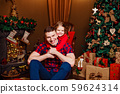 Child with dad near Christmas tree 59624314