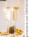 Pouring champagne wine into glasses over blur spots light background ready to bring in the New Year 59640059