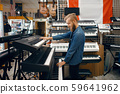 Young man choosing synthesizer in music store 59641962