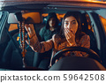 Female driver and hooded car hijacker on back seat 59642508