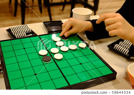 Child's hand playing an othello game 59644334