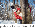 Woman and man in winter throwing snowball hiding behind a tree 59646158