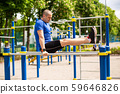 Man doing exercises on bars at sports ground 59646826