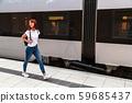 Young woman walking railway platform along train 59685437