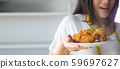 Young Asian woman holding fried chicken on plate, 59697627