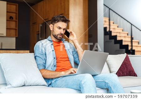 Young adult man talking on smartphone, using laptop, working at home 59707339