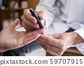 measuring the blood glucose level of an old man 59707915