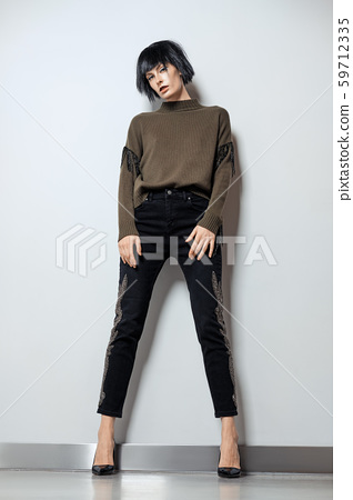 Fashion model in black wig, pullover with fringe 59712335