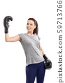 Girl with boxing gloves raising hand in celebration 59713766