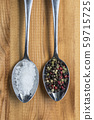 crystal salt and peppercorns on metal spoons 59715725
