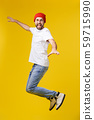 young casual man jumping for joy on yellow gold background 59715990