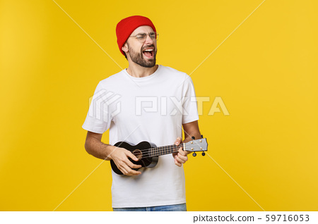close-up of funny young man playing a guitar. isolated on yellow gold background 59716053