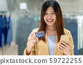 Portrait Asian woman using credit card with smart mobile phone for online shopping in department store over the clothes shop store background, technology money wallet and online payment concept 59722255
