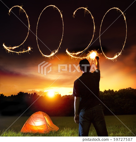 young man celebrating and drawing 2020 new year by 59727587