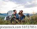 Young tourist couple travellers with tent shelter sitting in nature, resting. 59727851