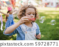 Small girl blowing bubbles outdoors in garden in summer. 59728771