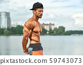 Man with perfect muscular body posing outdoors. 59743073