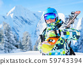 Portrait of sports man in helmet and mountain skis against background of mountains in afternoon 59743394