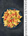 Mexican nachos, tortilla chips with tomato, avocado, and cilantro leaves, a top shot on a dark 59744454