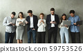 Businesspeople with gadgets standing in row over grey wall 59753526