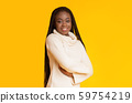 Successful afro girl smiling over yellow background 59754219