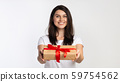 Girl Offering Wrapped Gift Box To Camera Standing, White Background 59754562
