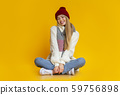 Cheerful young woman sitting on floor over yellow studio background 59756898